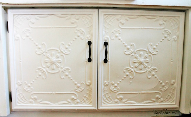 Give your kitchen cabinet doors vintage style by attaching metal ceiling tiles to the fronts - KnickofTime.net