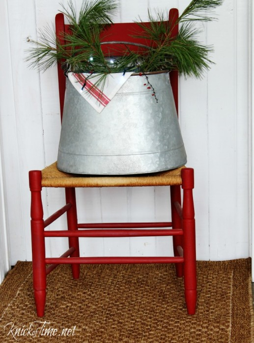 A rustic bucket filled with evergreen clippings, Christmas lights, with a red stripe towel peeking over the edge, makes charming farmhouse Christmas decor! | KnickofTime.net