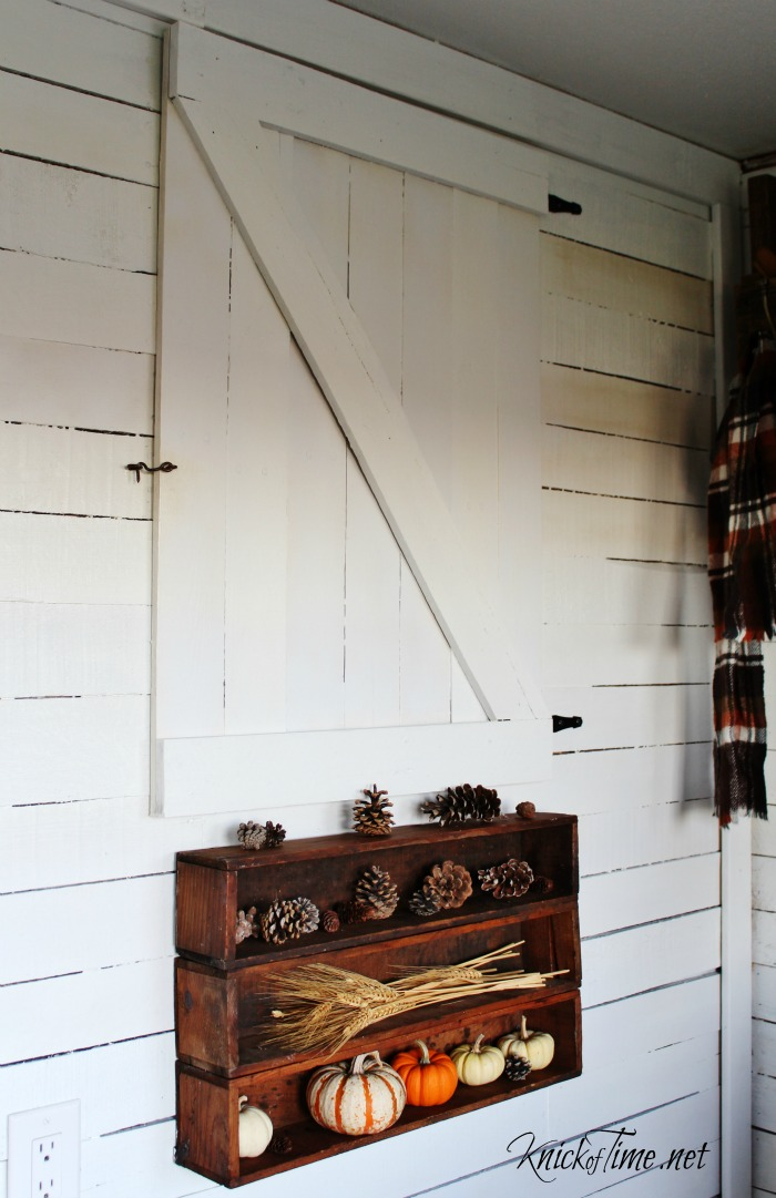 autumn decor in the entryway with antique crates, pumpkins, pine comes and wheat - KnickofTime.net