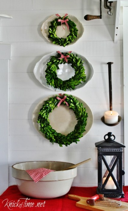 Add a festive ribbon to boxwood wreaths and hang them over vintage platters for simple farmhouse Christmas decor - KnickofTime.net