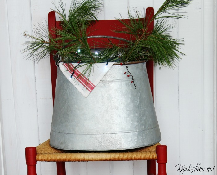 rustic bucket filled with greenery | Christmas entryway decor