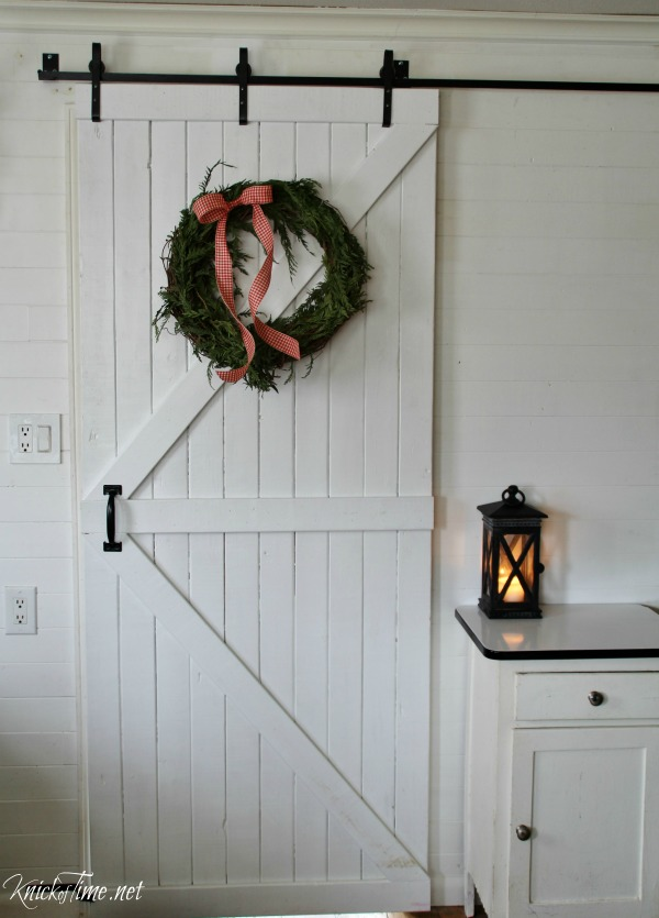 sliding barn door with Christmas wreath in farmhouse kitchen - KnickofTime.net