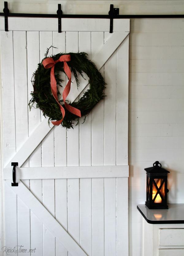 Farmhouse Christmas decorating ideas with sliding barn door and Christmas wreath - KnickofTime.net