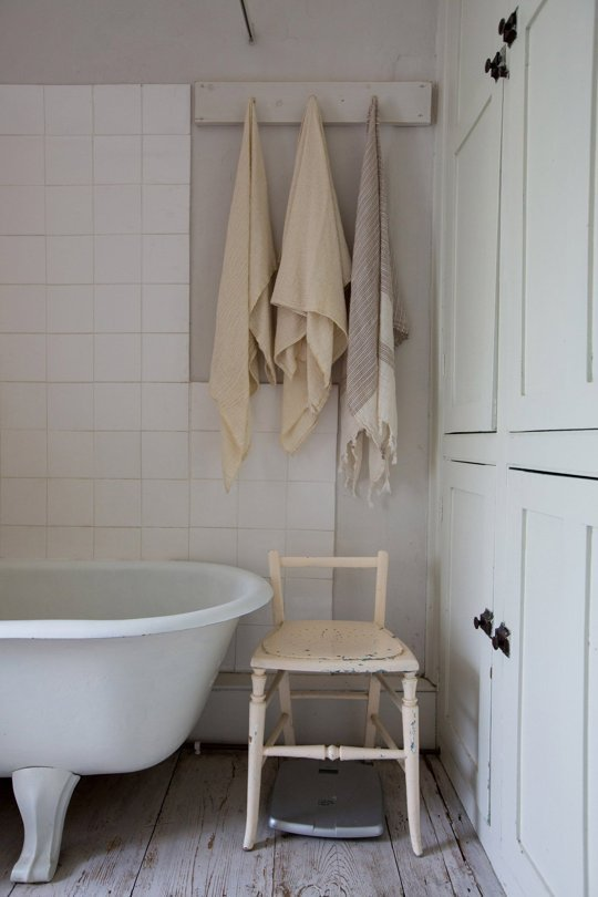 Use a simple peg rack as a towel rack in a farmhouse bathroom