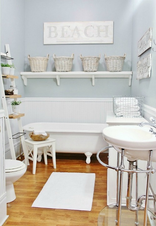 farmhouse bathroom with beach signs, beadboard walls and shelves with storage baskets