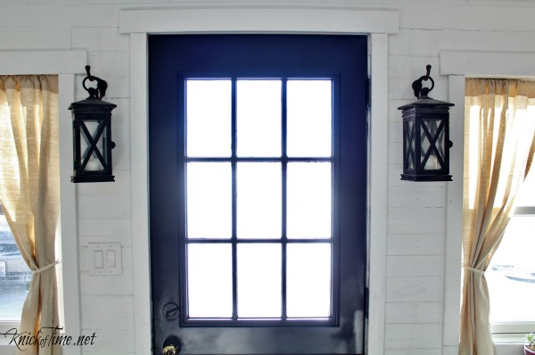 Cast iron hanging lanterns flank the front door of this farmhouse entryway. See the full remodel at KnickofTime.net