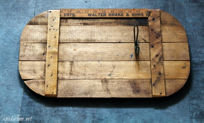 A vintage ruler and coat hook are helping to transform an old picnic basket lid into farmhouse wall hooks - KnickofTime.net