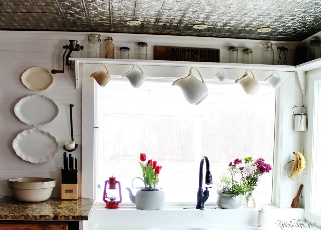 Hanging ironstone pitchers in a farmhouse kitchen window saves counter space and makes a simple, but charming faux curtain! - www.knickoftime.net