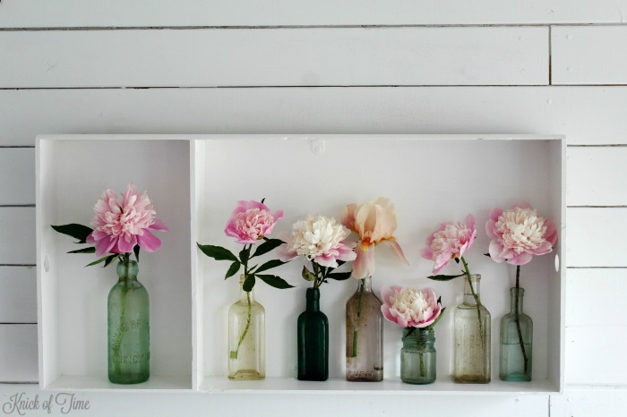 repurposed antique trunk tray displaying peonies in antique medicine bottles - KnickofTime.net