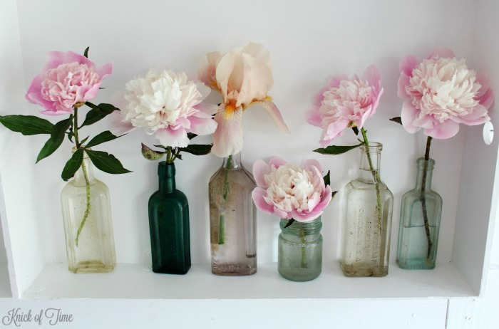 Display summer flowers in antique apothecary bottles for a vintage farmhouse look - KnickofTime.net