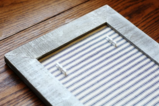 How to make a farmhouse style photo frame with a thrift store frame, ticking fabric, & mini clothespins|www.KnickofTime.net
