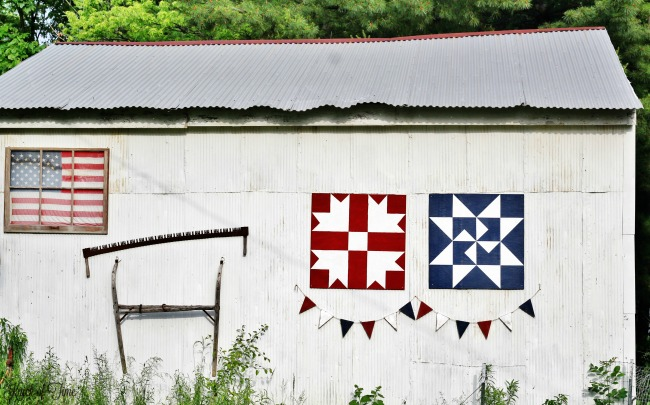Patriotic Barn Decorated with Red, White and Blue Barn Quilts and a Pennant Banner - KnickofTime.net