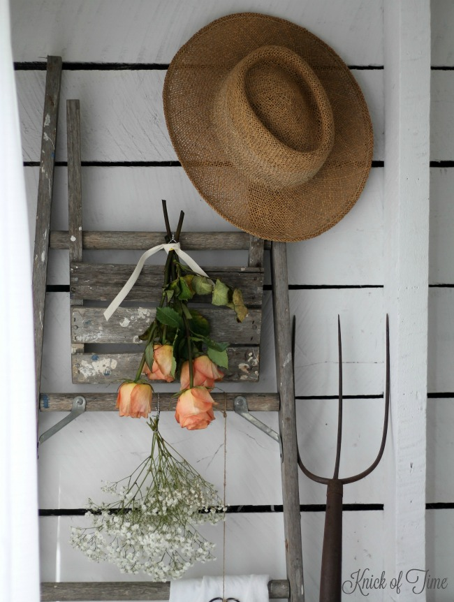 Easy farmhouse decor includes a rustic old ladder, a woven hat and a rusty old pitchfork. See more at www.knickoftime.net