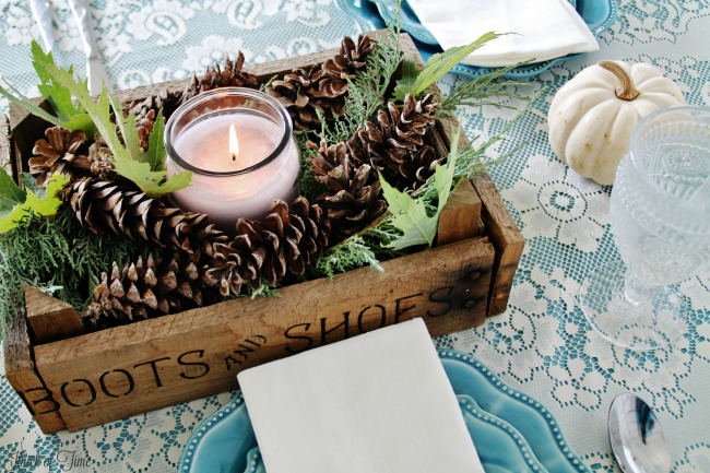 Fill a rustic crate with pine cones, pine branch clippings, leaves and a candle for a charming fall table centerpiece - www.knickoftime.net