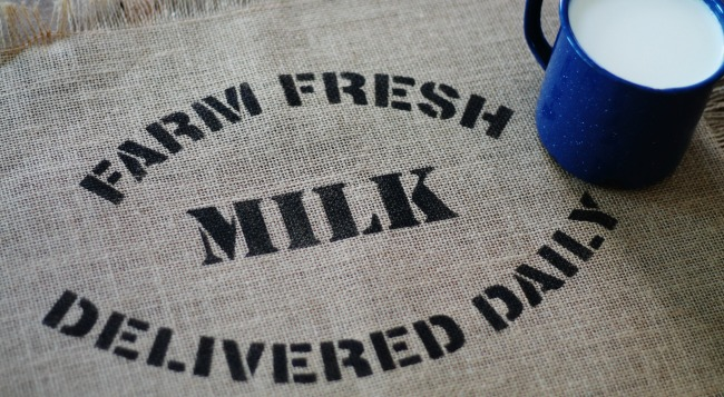 Burlap placemat with Knick of Time's Farm Fresh Milk stencil. Part of the farmhouse line of Vintage Sign Stencils - www.knickoftiime.net