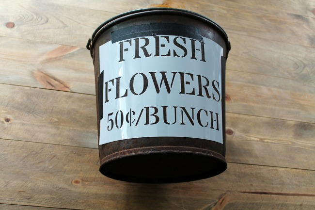 Stencil placement on a rusty metal bucket to make an industrial farmhouse trash can | knickoftime.net