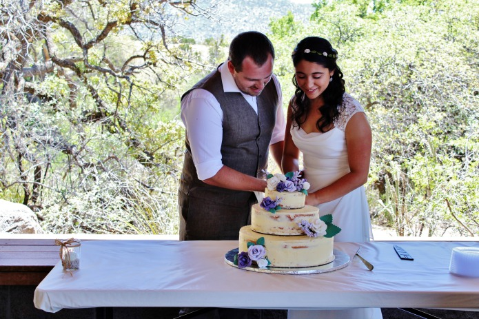 Cutting the purple flowers tiered wedding cake   www.knickoftime.net