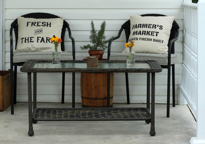 Farmhouse covered back porch decor with canvas pillows and faux wicker furniture