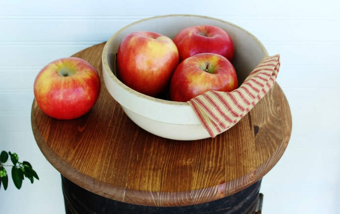 Red farmhouse fresh apples vignette on repurposed antique flour bin accent table by Knick of Time | www.knickoftime.net