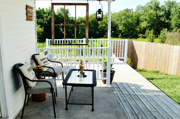 "Farmhouse covered porch with white railing and antique window to ""frame"" the view