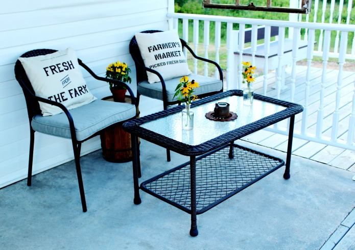 Farmhouse style pillows and wicker outdoor furniture on small covered patio | www.knickoftime.net