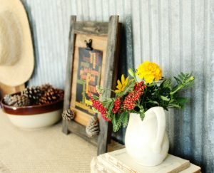 Rustic fall decorating with pine cones, wooden photo frame clipboard, and fall flowers on book stack