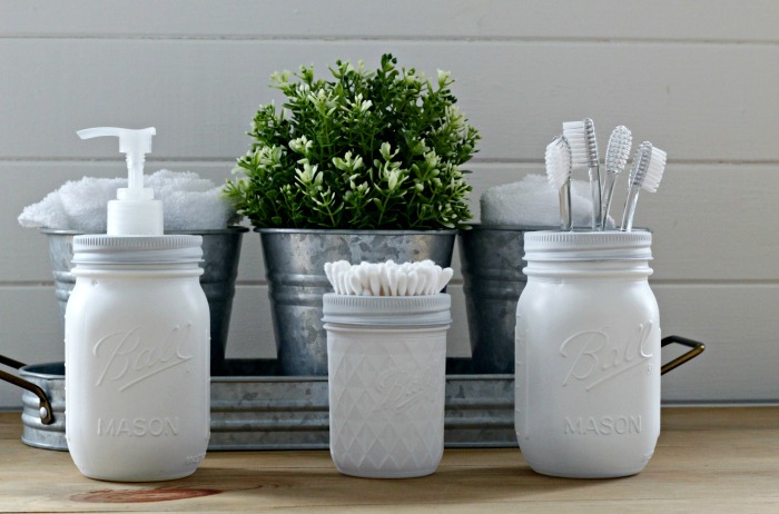 A farmhouse style set of bathroom storage white painted mason jars #knickoftime # farmhousestyle # bathroom # masonjars | www.knickoftime.net