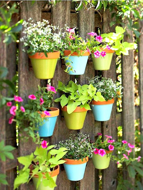 Painted flower pots on a fence. Such a great (and pretty idea!
