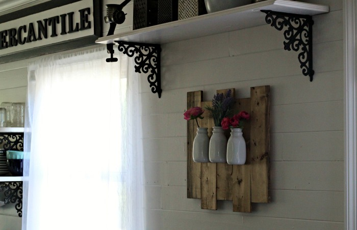 Make a Milk Bottle Hanging Wall Flower Vase on a pallet sign. It's an easy project and you can put faux flowers in it, or real blooms from your garden! Easy step-by-step instructions at Knick of Time | www.knickoftime.net #knickofTime #farmhousestyle #flowers #garden